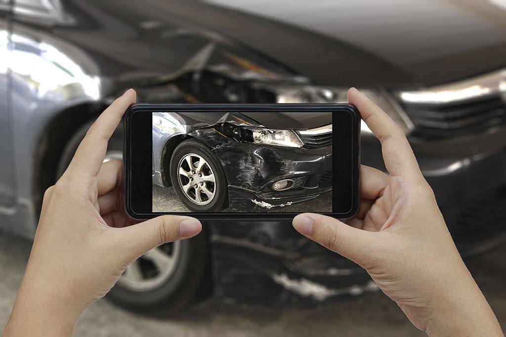 Taking a photo of auto collision damage.